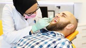 Un dentista en la comprobación del hijab dientes de los pacientes metrajes