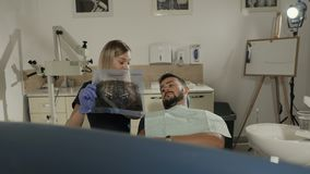 Un dentista femminile mostra i raggi x pazienti del ` s dei denti e discute loro ulteriore trattamento archivi video