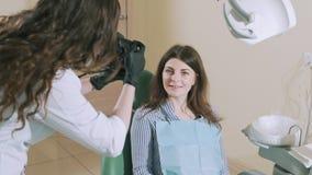 Un dentista oscuro-cabelludo toma imágenes de su paciente en una cámara profesional después del tratamiento dental para hacer un  almacen de video