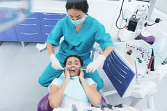 Un dentiste féminin soigne un patient Elle s'assied sur la chaise dentaire et a peur photographie stock