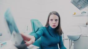 Un dentiste tenant un rayon X et expliqué au patient banque de vidéos