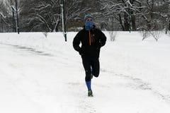 Un deportista corre en nieve imagenes de archivo