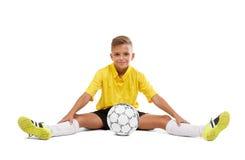 Un deportista joven lindo en una camiseta amarilla y pantalones cortos negros que se sientan en un piso aislado en un fondo blanc Imagen de archivo
