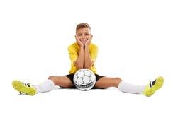 Un deportista joven lindo en una camiseta amarilla y pantalones cortos negros que se sientan en un piso aislado en un fondo blanc Fotografía de archivo libre de regalías