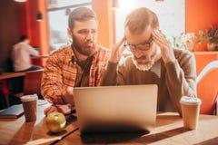 Un des types est bouleversé et regardant à l'écran de l'ordinateur portable tandis qu'un autre est à son ami avec l'espoir et le  Images stock
