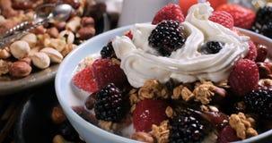 Un desayuno de cereales con las bayas, las frutas secas, la leche y la crema azotada almacen de metraje de vídeo
