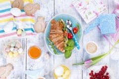Un desayuno de la familia de cruasanes con el cohete y queso y café aromático, huevos de diversos colores, platos brillantes y Pa Imagen de archivo