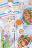 Un desayuno de la familia de cruasanes con el cohete y queso en una placa azul y un café fragante, huevos de diversos colores y u Fotos de archivo libres de regalías