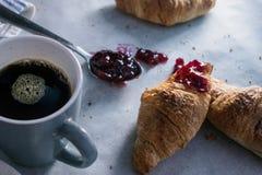 Un desayuno del domingo por la mañana con los cruasanes y el café fotografía de archivo
