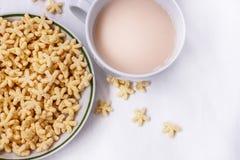 Un desayuno sano de las avenas, de la leche y del té en una tabla blanca imagen de archivo libre de regalías