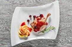 Un desayuno sano del confit de las piernas del pato con Apple caramelizado sirvió en una placa blanca Foto de archivo