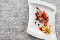 Un desayuno sano del confit de las piernas del pato con Apple caramelizado sirvió en una placa blanca Foto de archivo libre de regalías