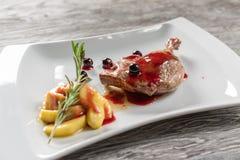 Un desayuno sano del confit de las piernas del pato con Apple caramelizado sirvió en una placa blanca Imagen de archivo