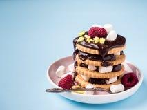 Un dessert doux d'une framboise de biscuit de chocolat et d'une tasse de guimauve de café sur une table bleu-clair Photo libre de droits