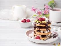 Un dessert doux d'une framboise de biscuit de chocolat et d'une tasse de guimauve de café sur une table légère Photo stock
