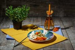 Un dessert freddo con il physalis e frutti secchi su un piatto e su un fondo variopinto Una bevanda calda vicino ad un gelato Fotografia Stock