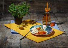 Un dessert freddo con il physalis e frutti secchi su un piatto e su un fondo variopinto Una bevanda calda vicino ad un gelato Fotografia Stock Libera da Diritti