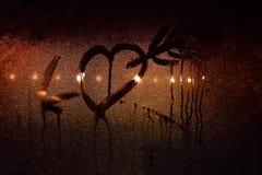 Un dessin d'un coeur percé par la flèche du ` s de cupidon sur le verre en sueur de la voiture dans la ville rétro-éclairée s'all Image stock