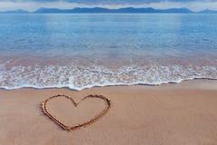 Un dessin d'un coeur comme symbole d'amour sur un à sable jaune en mer Photographie stock libre de droits