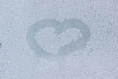 Un dessin de coeur sur une fenêtre congelée Photos libres de droits