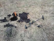 Un detector de metales y una pala en un fondo de la hierba seca imagen de archivo libre de regalías