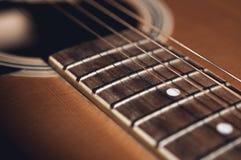Un dettaglio della chitarra acustica con la scenetta scura immagine stock