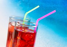 Un dettaglio di due vetri del cocktail rosso con la spiaggia della sfuocatura e dello spazio per testo Immagine Stock