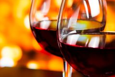 Un dettaglio di due vetri del vino rosso contro il fondo unfocused variopinto delle luci Immagine Stock