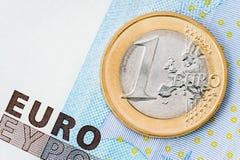 Un dettaglio di una euro moneta sul fondo della banconota Immagini Stock Libere da Diritti