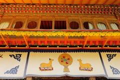 Un Dharma-cakra entre dos cabras del arrodillamiento Fotografía de archivo