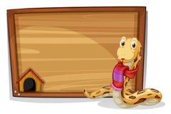 Un di legno svuota il bordo con un serpente Fotografia Stock Libera da Diritti