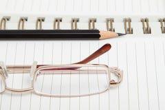 Un diario con una matita ed i vetri Fotografia Stock
