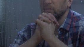 Un dieu de prière masculin d'une cinquantaine d'années derrière la fenêtre pluvieuse, espérant meilleur, croyance banque de vidéos