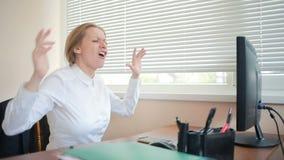 Un directeur féminin est fatigué du travail à une table dans le bureau et danse clips vidéos