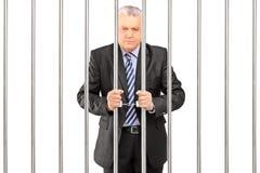 Un directeur menotté dans le costume posant en prison et tenant des barres Photos stock