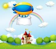 Un dirigeable avec une bannière vide au-dessus d'un château Image libre de droits