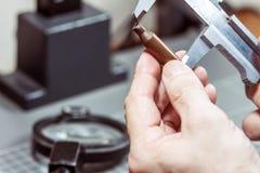 Un dirigeant légal de service mesure l'étui d'une arme à feu avec un calibre et conduit un examen ballistique Fin-u images libres de droits