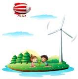 Un dirigible sobre una isla con un molino de viento Imagenes de archivo