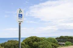 Un disabile o una sedia a rotelle che parcheggia soltanto segno ad una spiaggia che osserva il pl Fotografia Stock