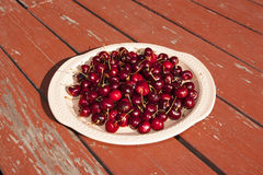 Un disco de cerezas en una mesa de picnic rústica Imagenes de archivo