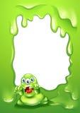 Un diseño verde de la frontera con un monstruo verde asustadizo Imagen de archivo
