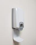 Un dispensador del jabón en una pared blanca Foto de archivo libre de regalías