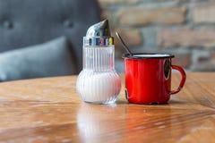 Un dispositif trembleur de tasse et de sucre d'émail sur une table Image stock
