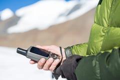 Un dispositivo de los gps en una mano contra las montañas nevadas foto de archivo