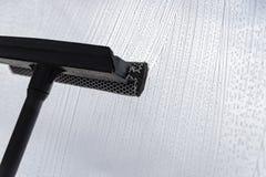 Un dispositivo especial para lavar ventanas hace espuma líquido en la superficie de cristal imagenes de archivo