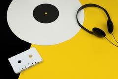 Un disque vinyle de long jeu blanc avec un écouteur noir et une bande blanche de cassette sonore photo libre de droits