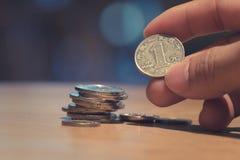 Un dito dell'uomo che tiene una moneta con la pila della moneta sul fondo del bokeh Fotografia Stock Libera da Diritti