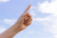 Un dito e una mano che raggiungono verso i precedenti del cielo blu Fotografia Stock