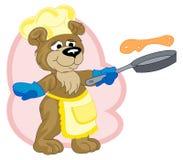 Un divertido cocinar-lleva está friendo las crepes Imagen de archivo