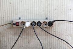 Un divisor eléctrico viejo con los zócalos y los alambres con los enchufes atados a diversos lados con un interruptor rojo quebra imagen de archivo